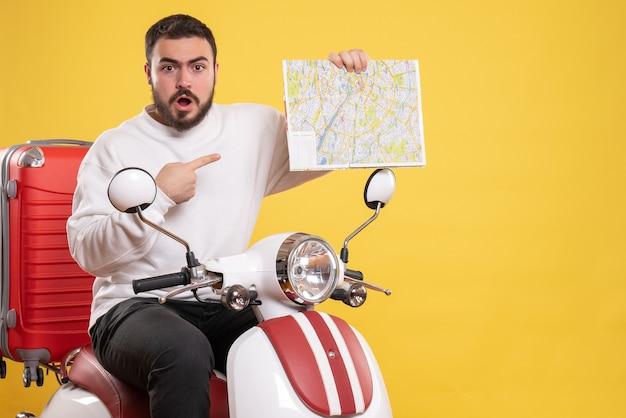 Bovenaanzicht van nieuwsgierige jonge kerel zittend op motorfiets met koffer erop met kaart op geïsoleerde gele achtergrond