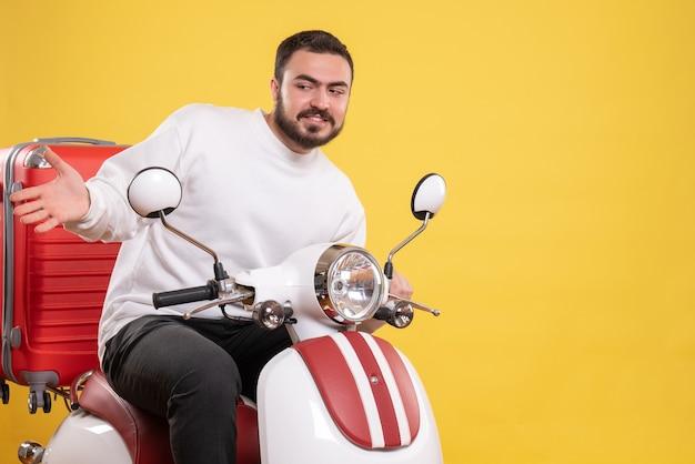 Bovenaanzicht van nieuwsgierige jonge kerel zittend op motorfiets met koffer erop op geïsoleerde gele achtergrond