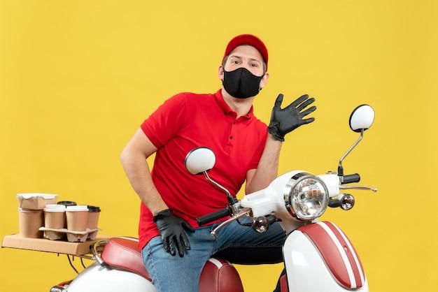 Bovenaanzicht van nieuwsgierige jonge volwassene met rode blouse en muts handschoenen in medisch masker leveren bestelling zittend op scooter op gele achtergrond