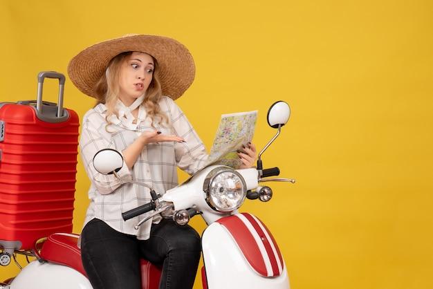 Bovenaanzicht van nieuwsgierige jonge vrouw die hoed draagt en op motorfiets zit en kaart op geel bekijkt