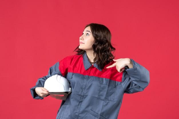 Bovenaanzicht van nieuwsgierige vrouwelijke architect die een harde hoed vasthoudt en deze op een geïsoleerde rode achtergrond richt