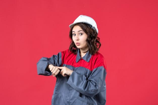 Bovenaanzicht van nieuwsgierige vrouwelijke bouwer in uniform met harde hoed en het controleren van haar tijd op geïsoleerde rode achtergrond