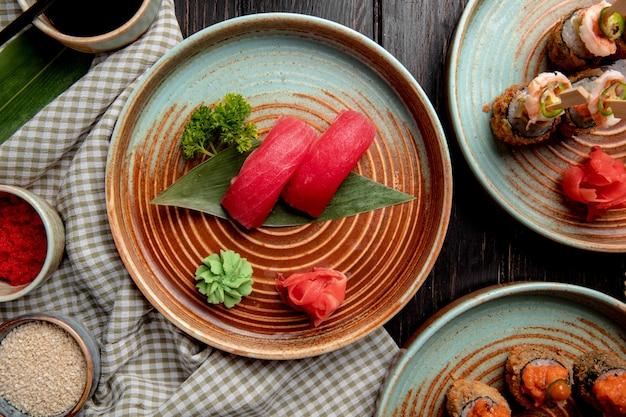 Bovenaanzicht van nigiri sushi met tonijn op bamboe blad geserveerd met ingelegde gemberplakken en wasabi op een bord