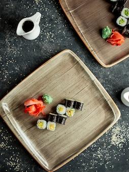 Bovenaanzicht van nori sushi met avocado geserveerd met gember en wasabi