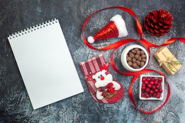 Bovenaanzicht van notebook en kerstman hoed en cornel chocolade nieuwjaar sok rode conifer kegel aan de linkerkant op donkere ondergrond