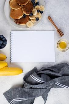 Bovenaanzicht van notebook en ontbijt pannenkoeken met plakjes banaan en bosbessen