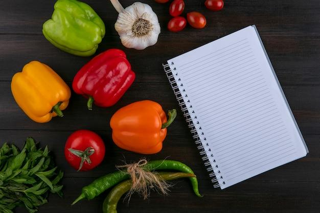 Bovenaanzicht van notebook met gekleurde paprika chilipepers knoflook bos van munt en tomaten op een houten oppervlak