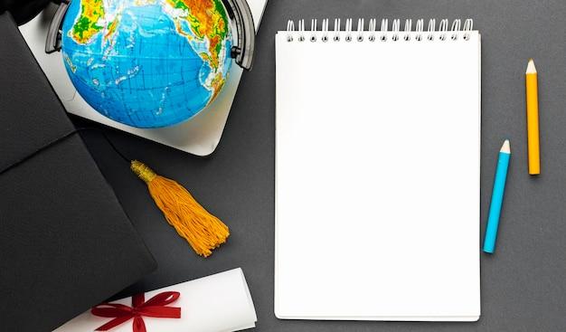 Bovenaanzicht van notebook met globe en potloden