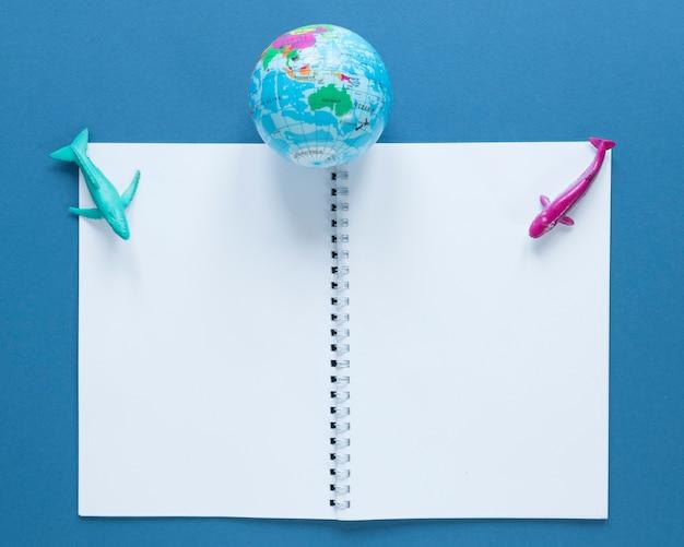 Bovenaanzicht van notebook met globe en vis beeldjes