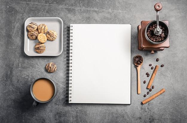 Bovenaanzicht van notebook met koffiekopje en grinder