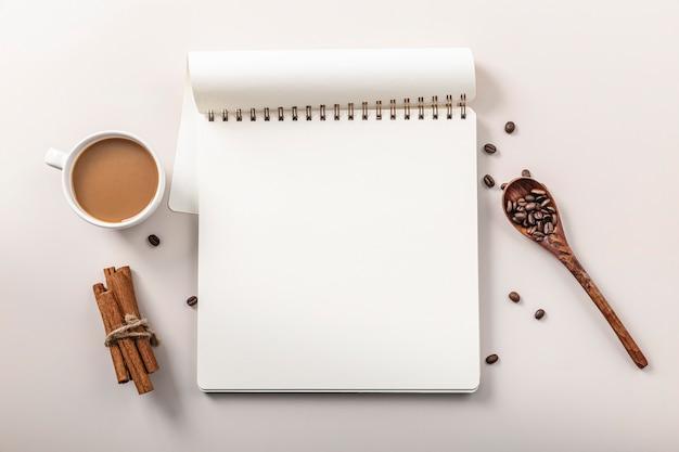 Bovenaanzicht van notebook met koffiekopje en kaneelstokjes