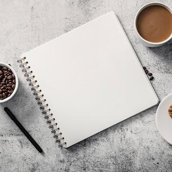 Bovenaanzicht van notebook met koffiekopje en pen