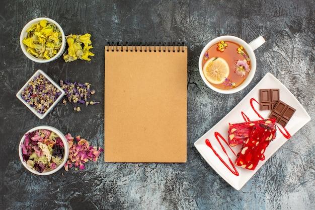 Bovenaanzicht van notebook met kommen met droge bloemen en een kopje thee bij een bord met chocolade