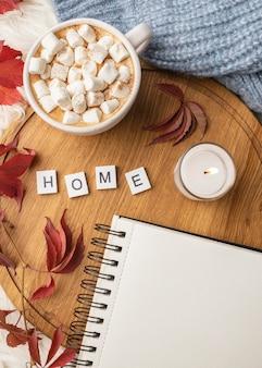 Bovenaanzicht van notebook met kop warme chocolademelk met marshmallows