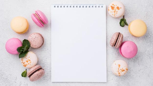 Bovenaanzicht van notebook met macarons en mint