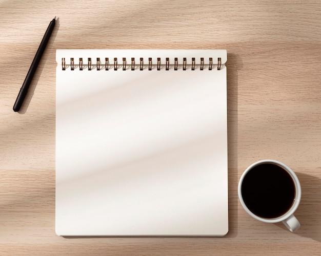 Bovenaanzicht van notebook met mok en pen
