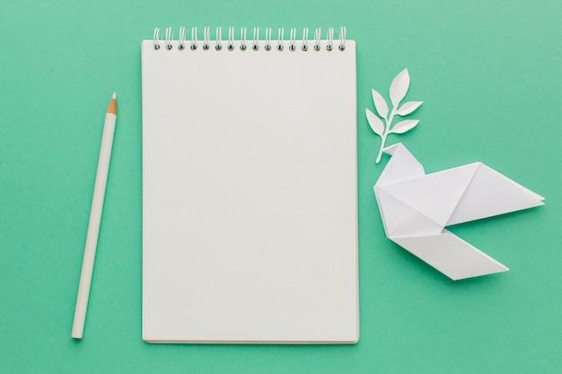 Bovenaanzicht van notebook met papieren duif en potlood