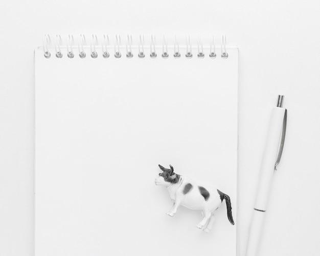 Bovenaanzicht van notebook met pen en dierlijk beeldje voor dierendag