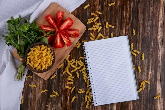 Bovenaanzicht van notebook met rauwe pasta in een kom met het snijden van plakjes tomaat op een snijplank met een bosje munt op een houten oppervlak