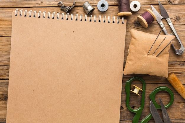 Bovenaanzicht van notebook met schaar en draad