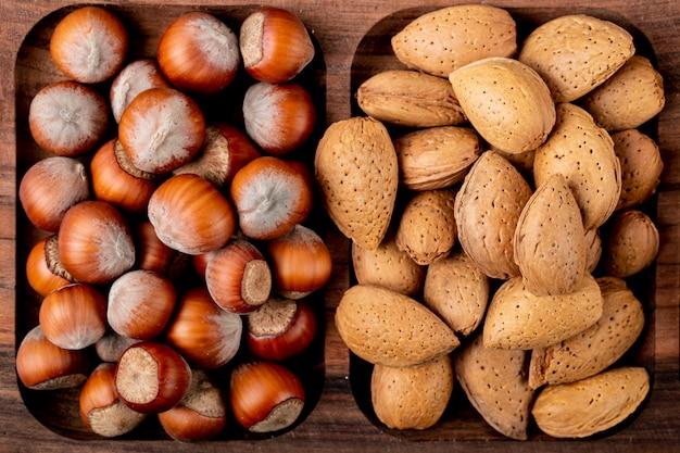 Bovenaanzicht van noten hazelnoten met amandelen in de schaal op een houten dienblad