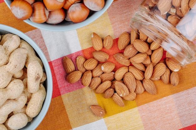 Bovenaanzicht van noten pinda's hazelnoten in kommen en amandel verspreid uit een glazen pot op geruite tafel servet
