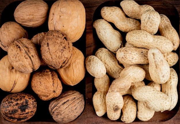 Bovenaanzicht van noten pinda's in shell en hele walnoten op houten achtergrond