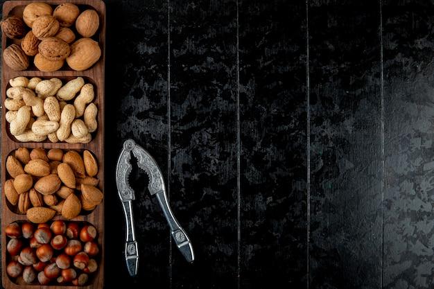 Bovenaanzicht van notenmix walnoten hazelnoten amandel en pinda's in de schaal met notenkraker op zwarte achtergrond met kopie ruimte