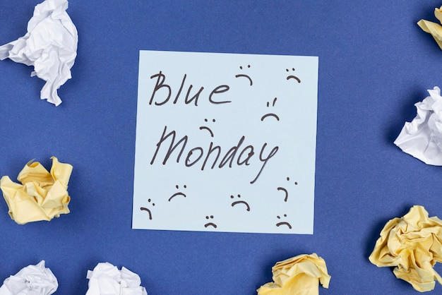 Bovenaanzicht van notitie met frons en verfrommeld papier voor blauwe maandag