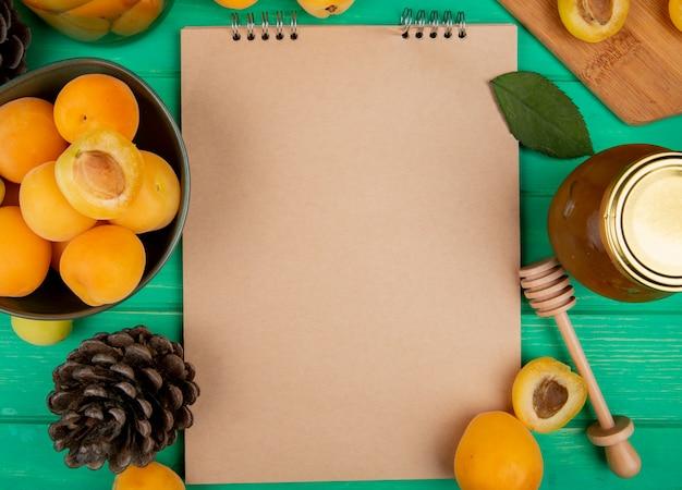 Bovenaanzicht van notitieblok met abrikozencompote jam en dennenappel op groene achtergrond met kopie ruimte
