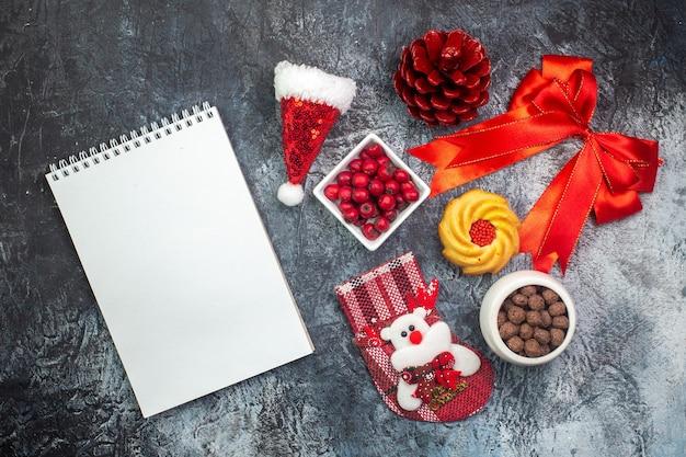 Bovenaanzicht van notitieboekje en heerlijke koekjes en cornel op een witte plaat nieuwjaarssok rood conifeerkegel rood lint op donkere ondergrond