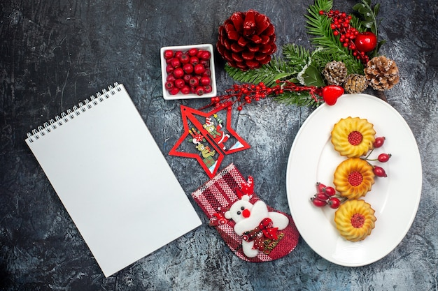 Bovenaanzicht van notitieboekje en heerlijke koekjes op een witte plaat en cornell in een kom dennentakken op een donkere ondergrond