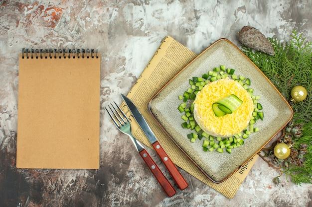 Bovenaanzicht van notitieboekje en smakelijke salade geserveerd met gehakte komkommer en mesvork op een oude krant