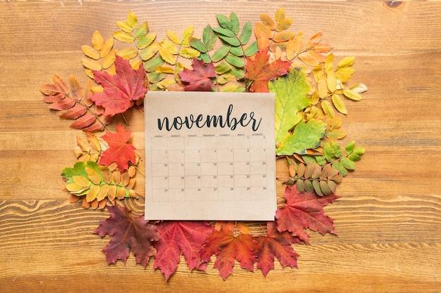 Bovenaanzicht van november kalenderblad omgeven door herfstbladeren van verschillende kleuren