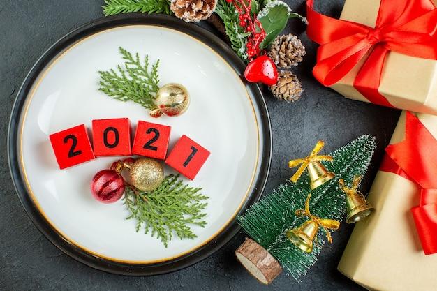 Bovenaanzicht van nummers decoratie accessoires op een plaat fir takken conifer kegel naast kerstboom op donkere achtergrond