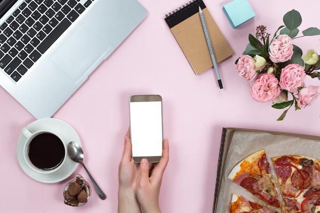 Bovenaanzicht van office-gadgets, koffie, mobiele telefoon en pizza
