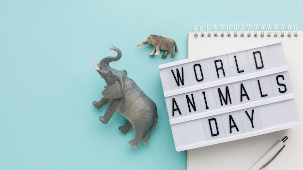 Bovenaanzicht van olifantenbeeldjes en lichtbak voor dierendag