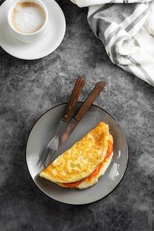 Bovenaanzicht van omelet met kaas en tomaten en een kopje koffie. gezonde zelfgemaakte omelet voor het ontbijt.
