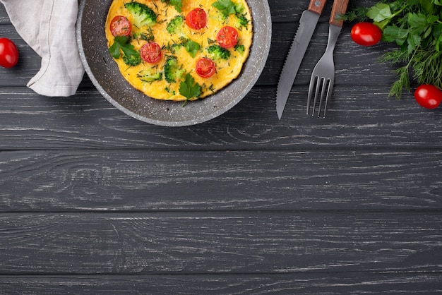 Bovenaanzicht van omelet voor ontbijt met tomaten en bestek