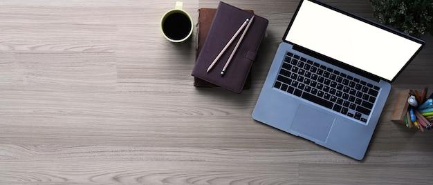 Bovenaanzicht van ondernemer tafel met opengeklapte laptopcomputer, notebook en koffiekopje op houten tafel. kopieer ruimte voor tekstinformatie of inhoud.