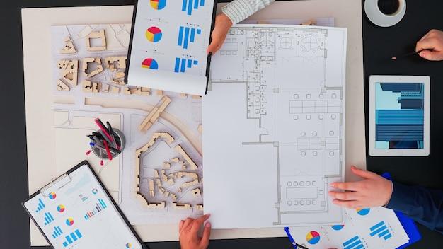 Bovenaanzicht van ondernemersteam van architecten met prototype van gebouwen, gadgets en papieren die aan de kantoortafel werken