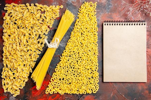 Bovenaanzicht van ongekookte pasta als een vorm van spaggetti manicotti en notebook op zwarte achtergrond