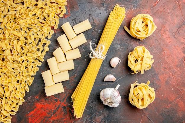 Bovenaanzicht van ongekookte pasta in verschillende vormen en knoflook op zwarte tafel