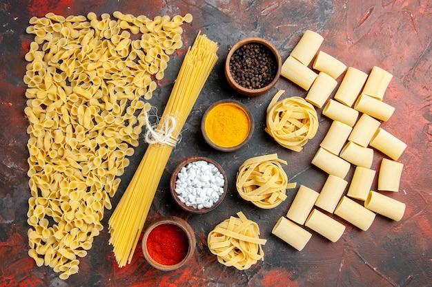 Bovenaanzicht van ongekookte pasta in verschillende vormen en verschillende kruiden op zwarte achtergrond