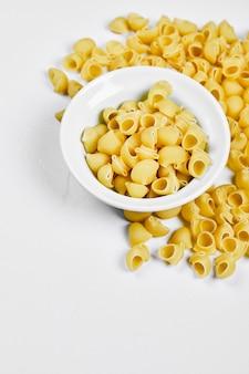 Bovenaanzicht van ongekookte pasta op witte tafel.