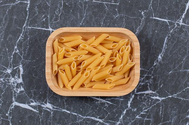 Bovenaanzicht van ongekookte pasta penne in houten kom.