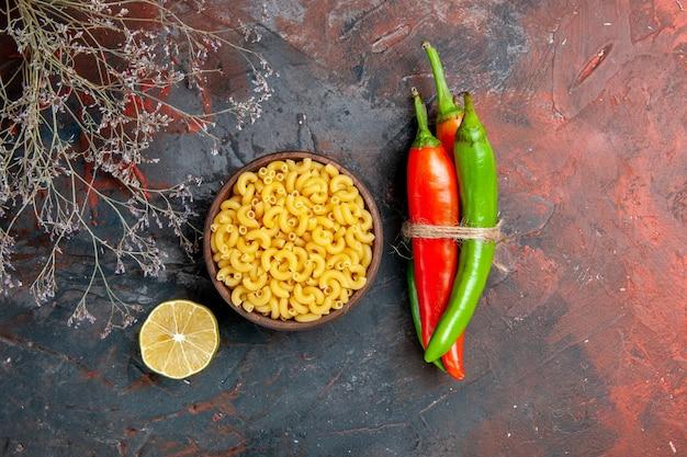 Bovenaanzicht van ongekookte pasta's cayennepeper in verschillende kleuren en maten in elkaar gebonden met touw en citroen op gemengde kleur achtergrond