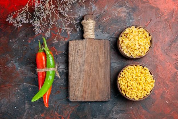Bovenaanzicht van ongekookte pasta's cayennepeper in verschillende kleuren en maten in elkaar gebonden met touw en houten snijplank op gemengde kleur achtergrond