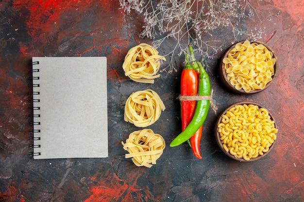 Bovenaanzicht van ongekookte pasta's cayennepeper in verschillende kleuren en maten in elkaar gebonden met touw en notitieboekje op gemengde kleur achtergrond