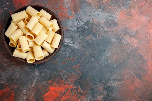 Bovenaanzicht van ongekookte pasta's in de pot aan de rechterkant van de zwarte tafel